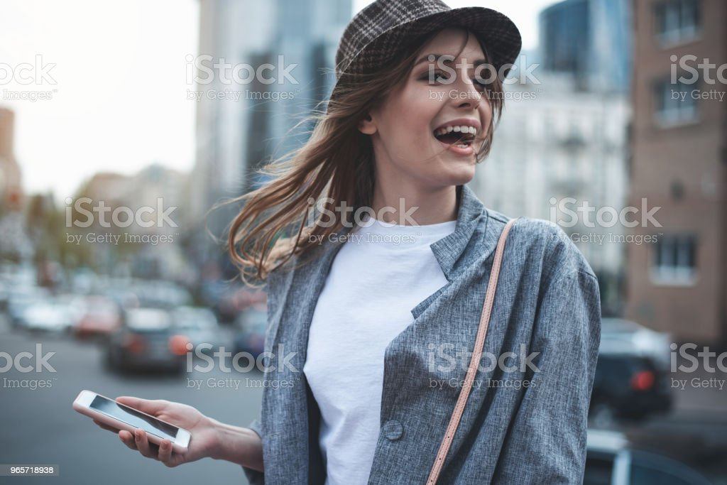 Young woman with phone is laughing in the street - Royalty-free Adult Stock Photo