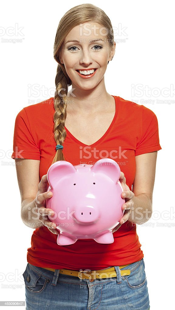 Young woman with piggybank Portrait of young woman holding a piggybank and smiling at camera. Studio shot, white background. 18-19 Years Stock Photo