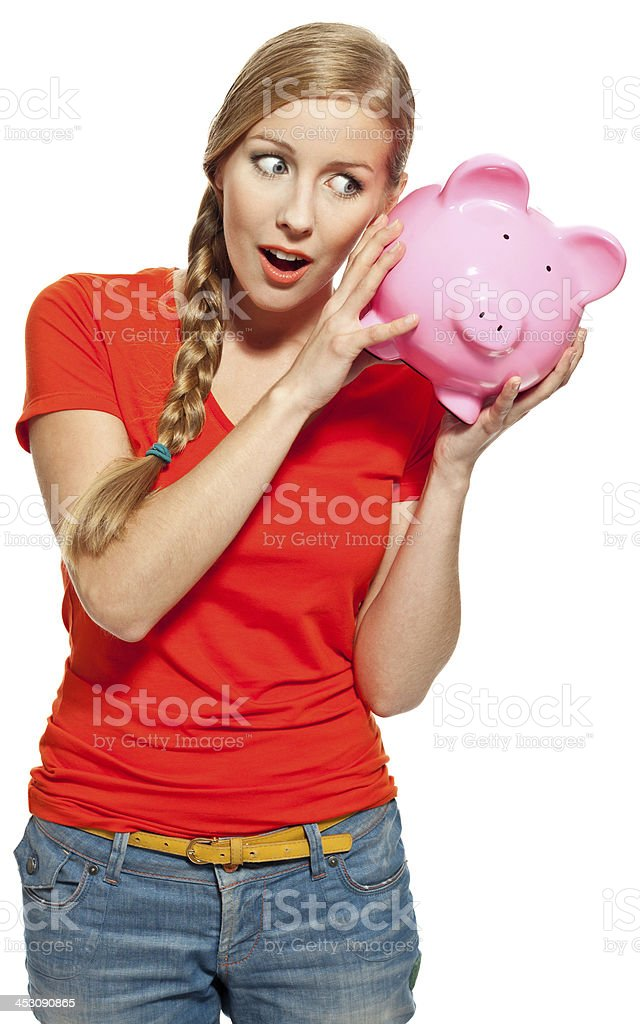 Young woman with piggybank Portrait of surprised young woman holding a piggybank. Studio shot, white background. 18-19 Years Stock Photo