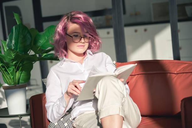 自宅でソファに座ってリラックスした本を読むピンクの髪を持つ若い女性。 - gen z ストックフォトと画像