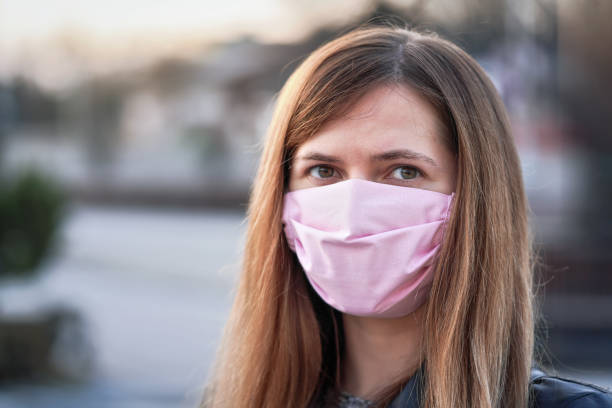 Young woman with pink hand made cotton face nose mouth mask portrait, blurred empty city behind her. Can be used during coronavirus covid-19 outbreak prevention stock photo