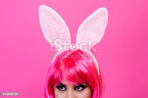 Close-up shot of a young woman with pink wig and rabbit ears isolated on the pink background