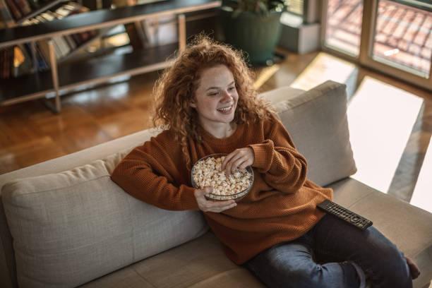 Junge Frau mit Popcorn fernsehen zu Hause – Foto