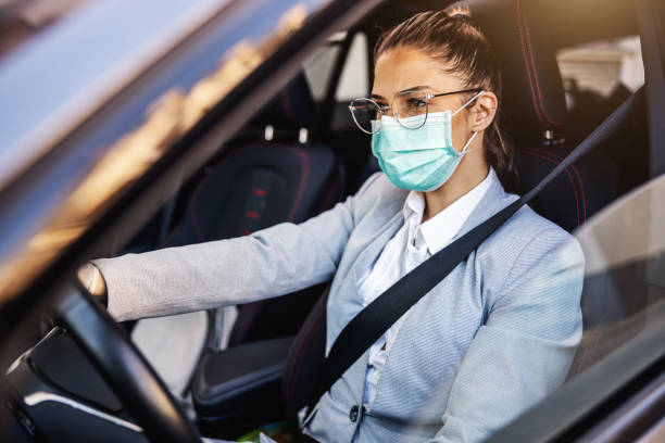 Young woman with protective mask and gloves driving a car. Infection prevention and control of epidemic. World pandemic. Stay safe. stock photo
