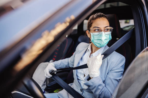 Young woman with protective mask and gloves driving a car putting safety belt on. Infection prevention and control of epidemic. World pandemic. Stay safe. stock photo