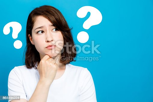 istock young woman with question marks. 864494224