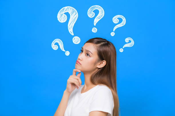 young woman with question marks. young woman with question marks. shrugging stock pictures, royalty-free photos & images