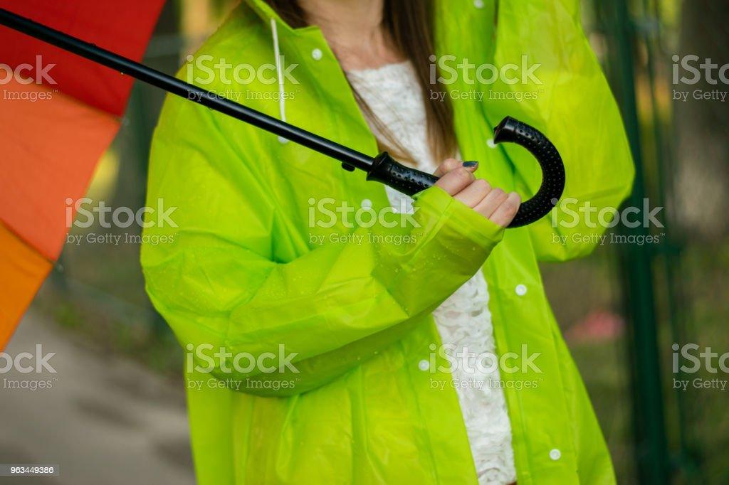 Młoda kobieta z płaszczem przeciwdeszczowym trzymającym tęczowy parasol - Zbiór zdjęć royalty-free (20-29 lat)