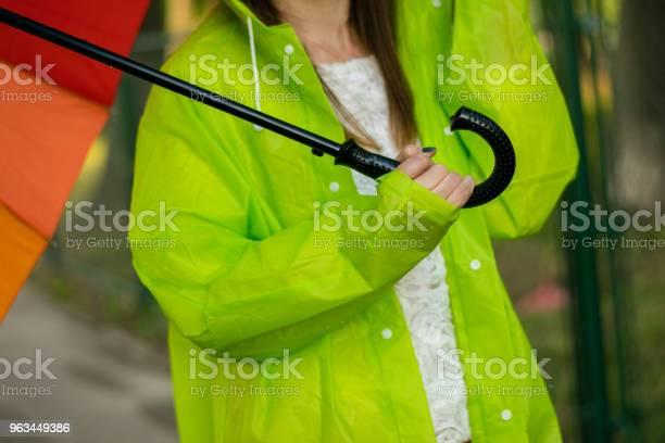 Młoda Kobieta Z Płaszczem Przeciwdeszczowym Trzymającym Tęczowy Parasol - zdjęcia stockowe i więcej obrazów 20-29 lat