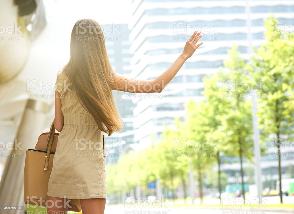 Young woman with raised arm waving for taxi stock photo