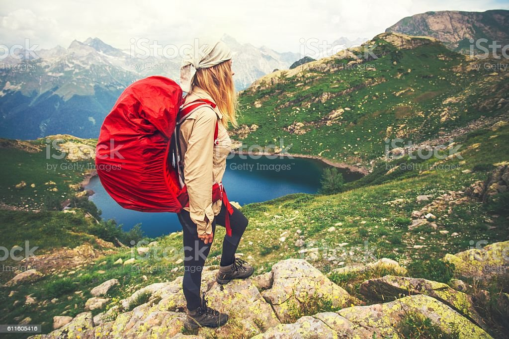 Young Woman with red backpack mountaineering Travel Lifestyle concept stock photo