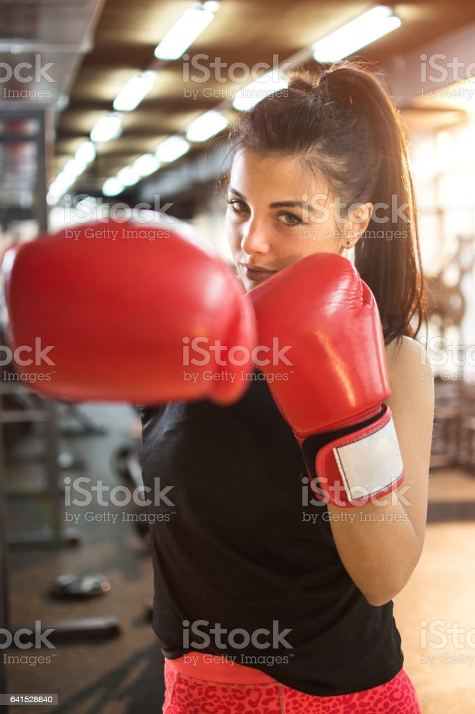 Young woman with red boxing gloves punching towards camera. - foto de acervo