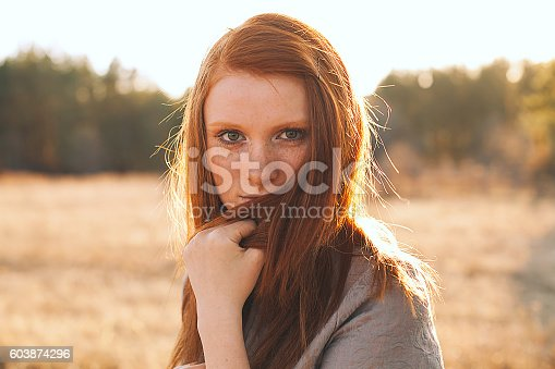 Portrait of Beauty Teenage Model Girl with Red Hair on the Background of Nature on the Field in Sun Light. Face of Young Woman with Freckles. Autumn. Glow Sun, Sunshine. Backlit. Warm Color Tones