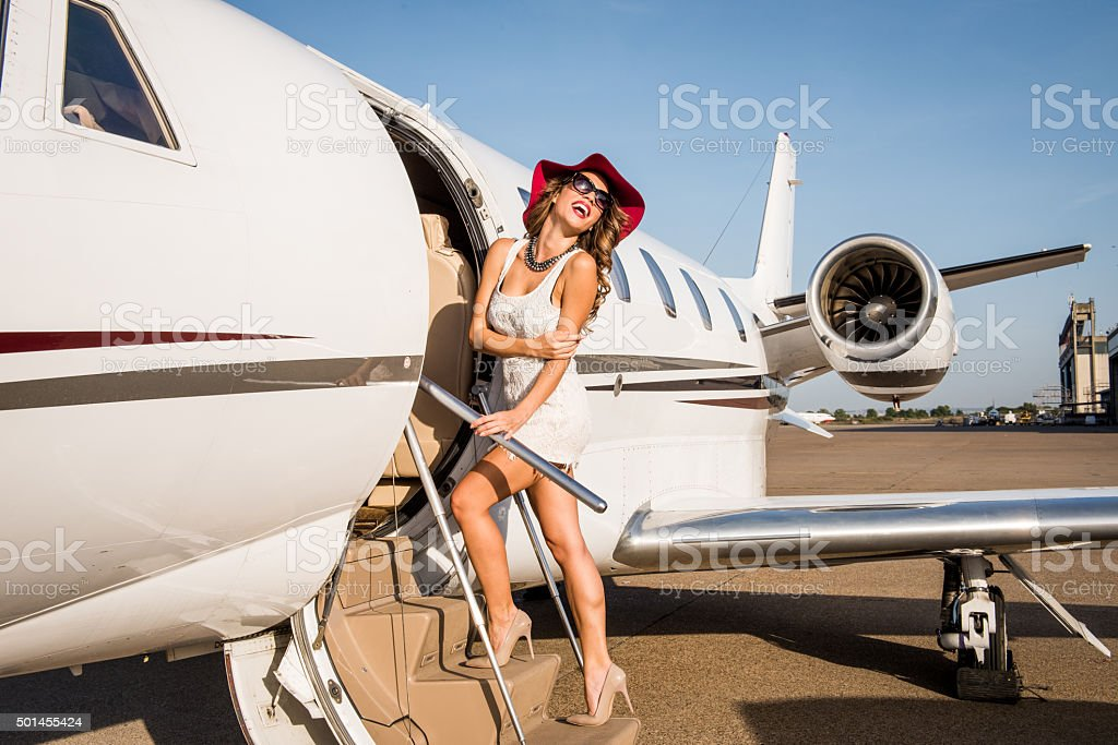 Young woman with red hat entering the aeroplane stock photo