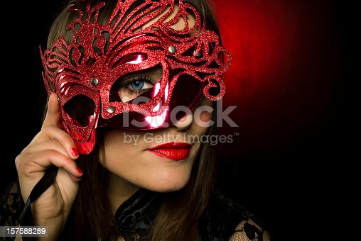 Attractive female with blue eyes looking through the mask