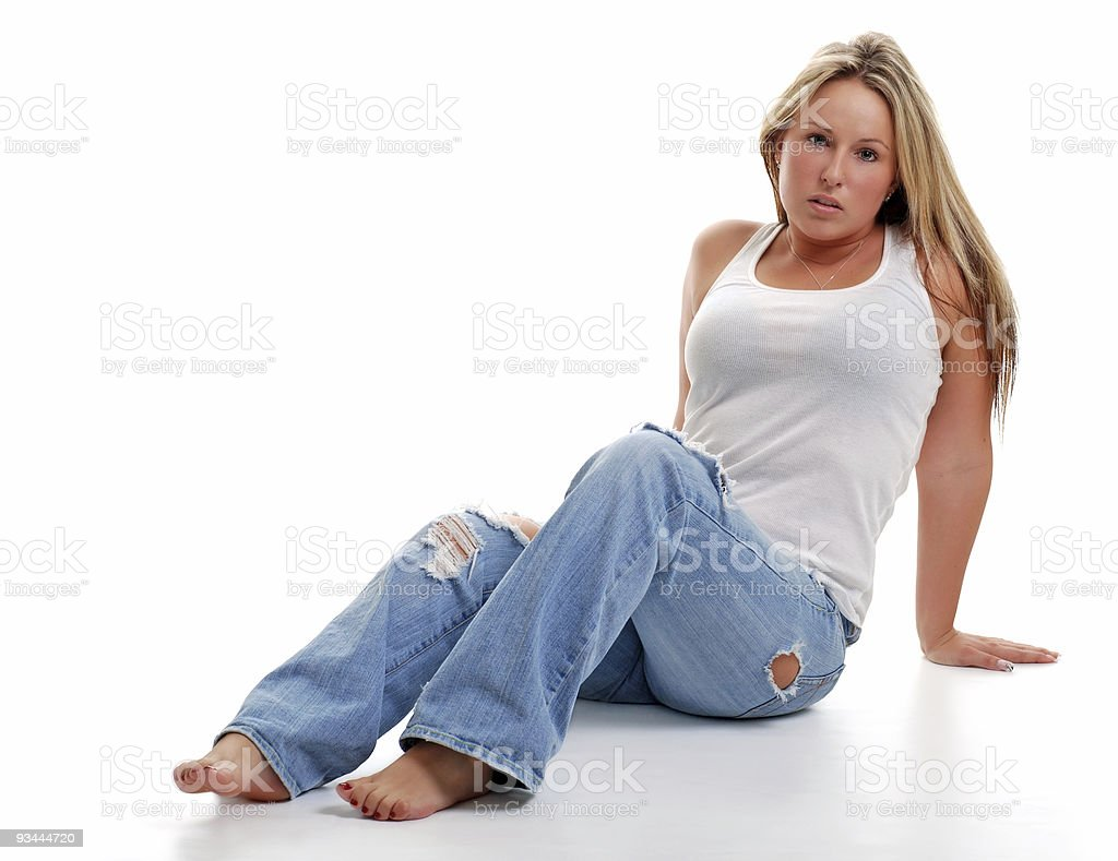 young woman with ripped jeans sitting down stock photo