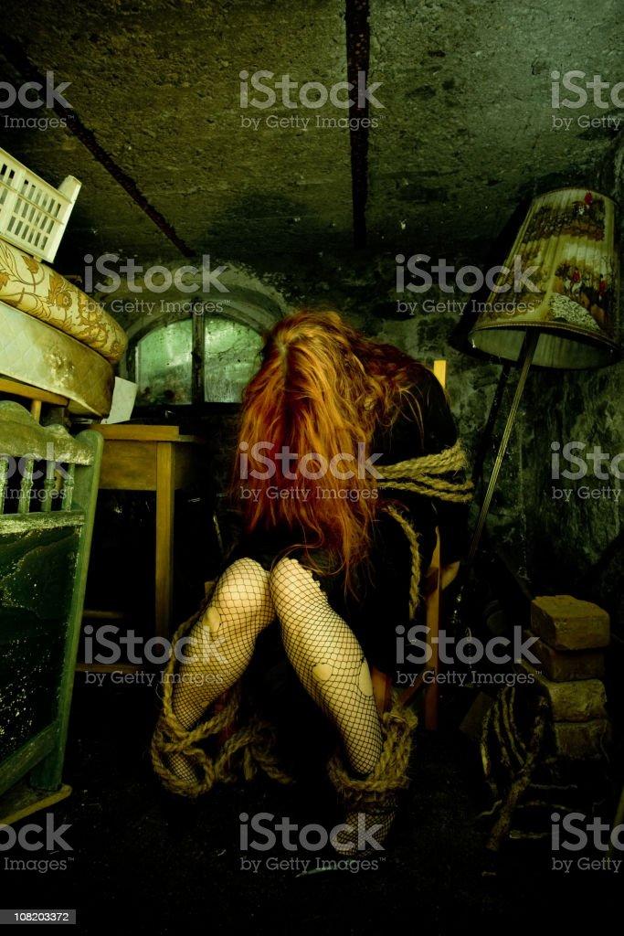 Mujer joven con cable alrededor de los tobillos in Dirty bodega - foto de stock