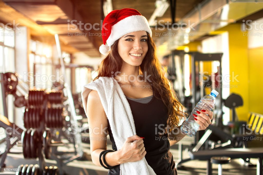 Young woman with Santa hat, bottle of water and towel in the gym. New Year. Christmas, holidays, fitness, and gym concept. stock photo