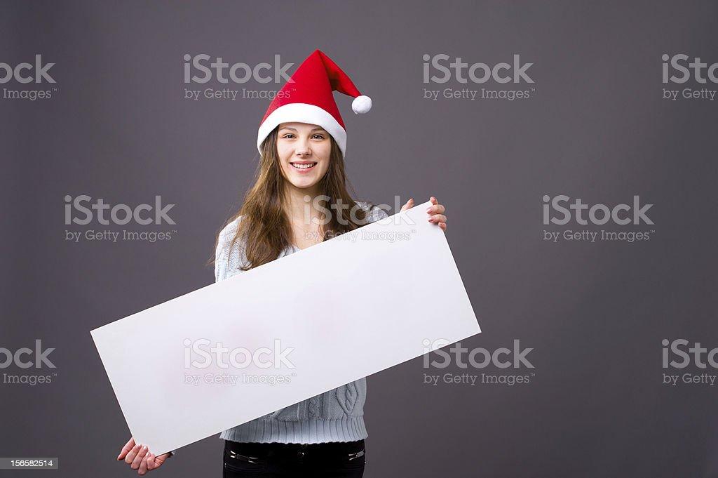 Junge Frau mit Weihnachtsmütze hält Transparent – Foto