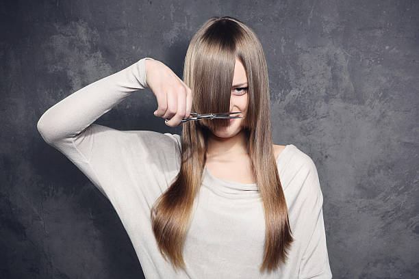 young woman with scissors trimming her bangs - cutter stock pictures, royalty-free photos & images