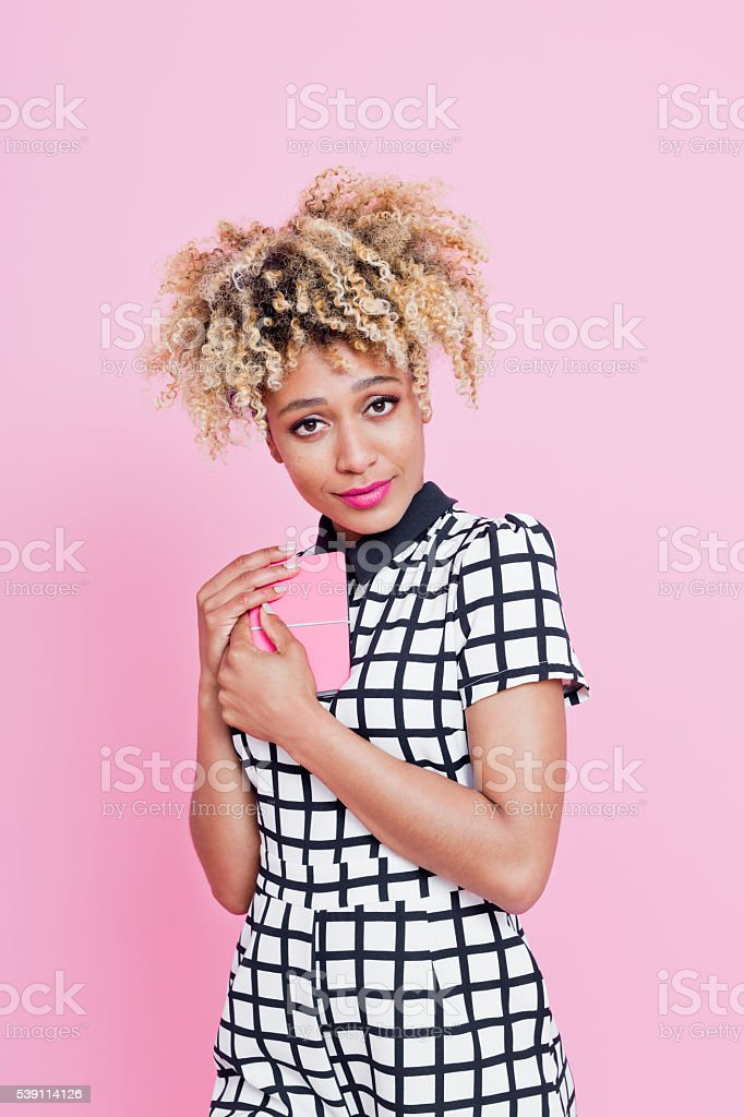 Young woman with secret notebook Summer portrait of happy, afro american young woman wearing grid check playsuit, standing against pink background, holding her pink diary, looking at camera. 20-24 Years Stock Photo