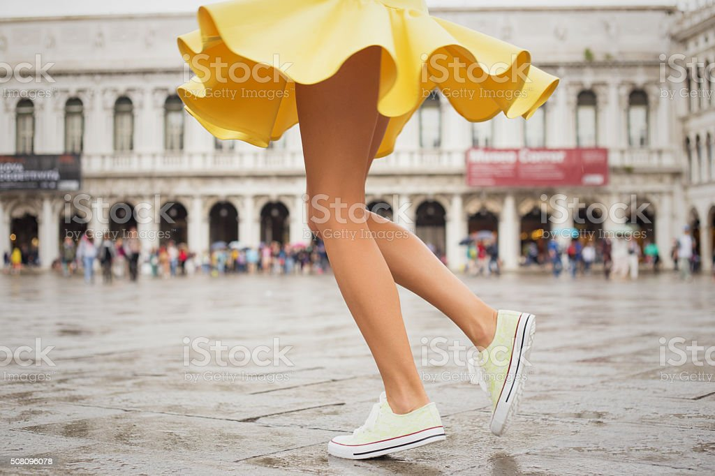Young woman with sexy legs and yellow skirt stok fotoğrafı