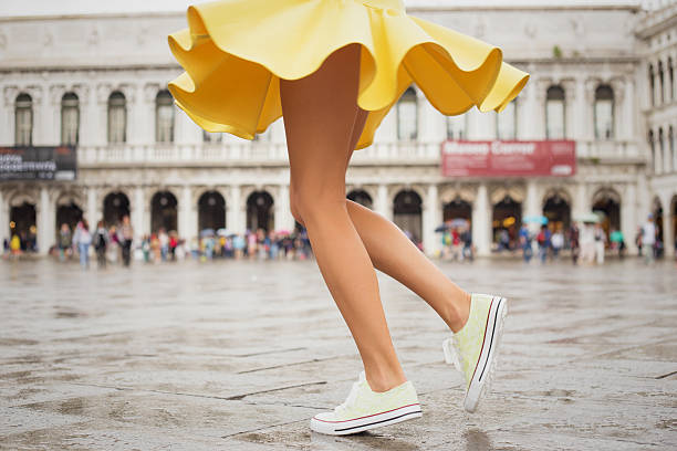 Young woman with sexy legs and yellow skirt stock photo