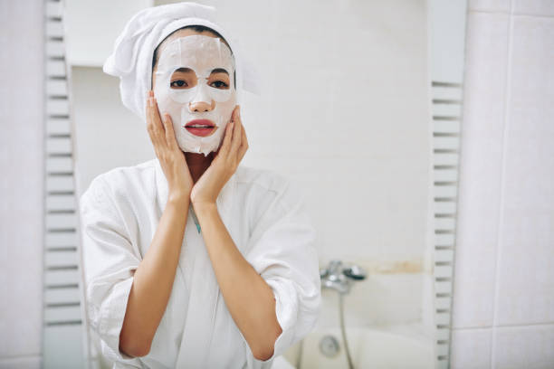 Young woman with sheet mask stock photo