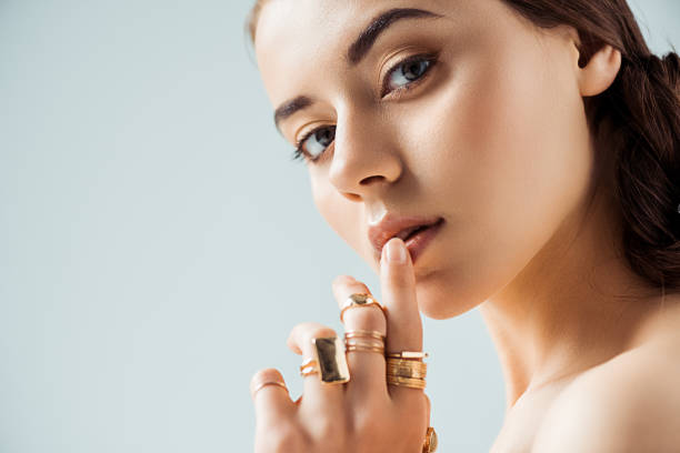 young woman with shiny makeup and golden rings touching lips isolated on grey young woman with shiny makeup and golden rings touching lips isolated on grey jewelry stock pictures, royalty-free photos & images