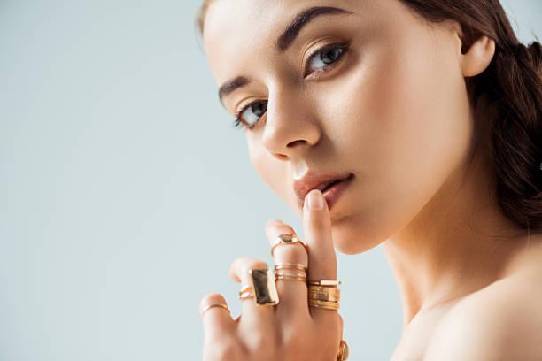 ung kvinna med glänsande makeup och gyllene ringar röra läpparna isolerade på grå - ädelsten bildbanksfoton och bilder