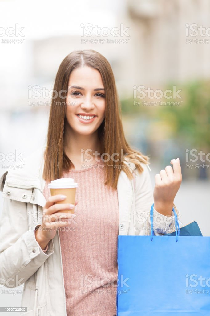 Young woman with shopping bag and coffee outdoors stock photo
