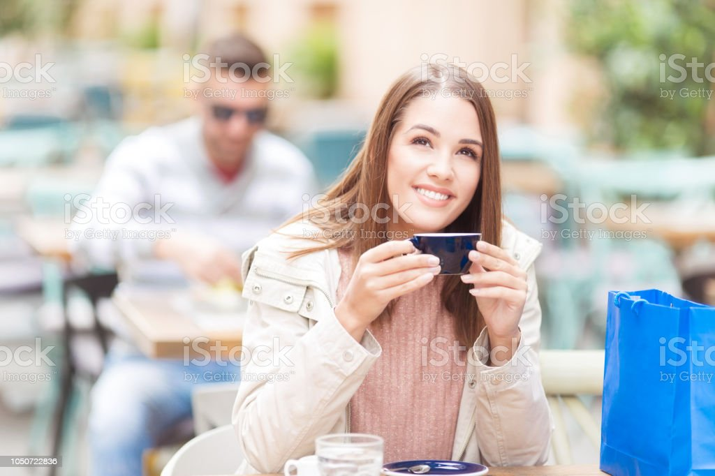 Young woman with shopping bag and coffee sitting in a cafe outdoors stock photo
