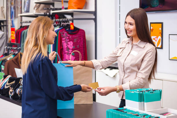 Young woman with shopping bag giving her credit card to seller in clothing shop Beautiful young woman with shopping bag giving her credit card to seller in clothing shop salesman stock pictures, royalty-free photos & images
