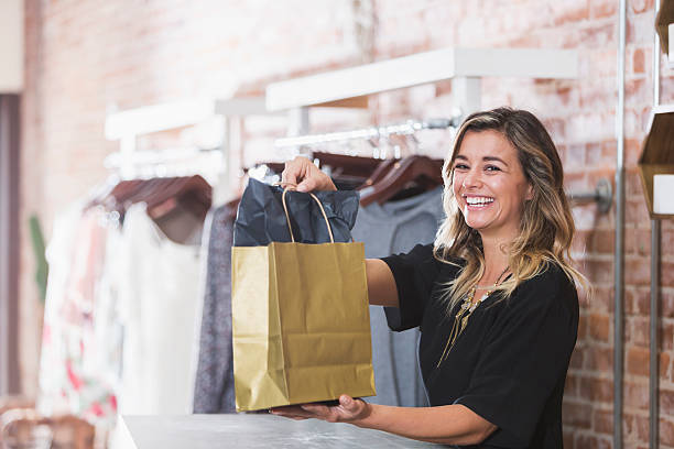 young woman with shopping bag in clothing store - store counter stock photos and pictures
