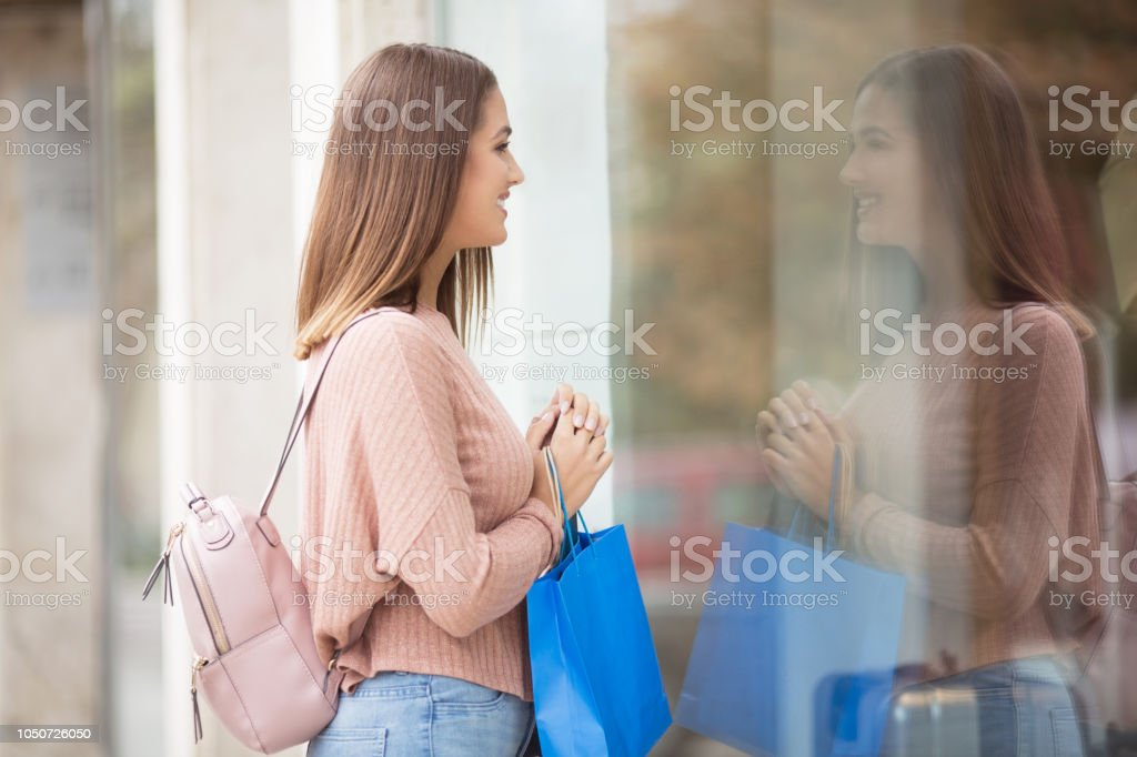 Young woman with shopping bag in front of a store outdoors stock photo
