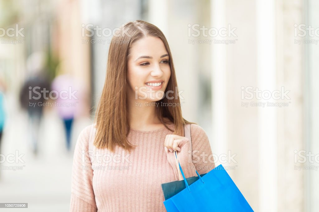 Young woman with shopping bag outdoors stock photo