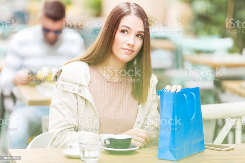 Young woman with shopping bag sitting in a cafe outdoors stock photo