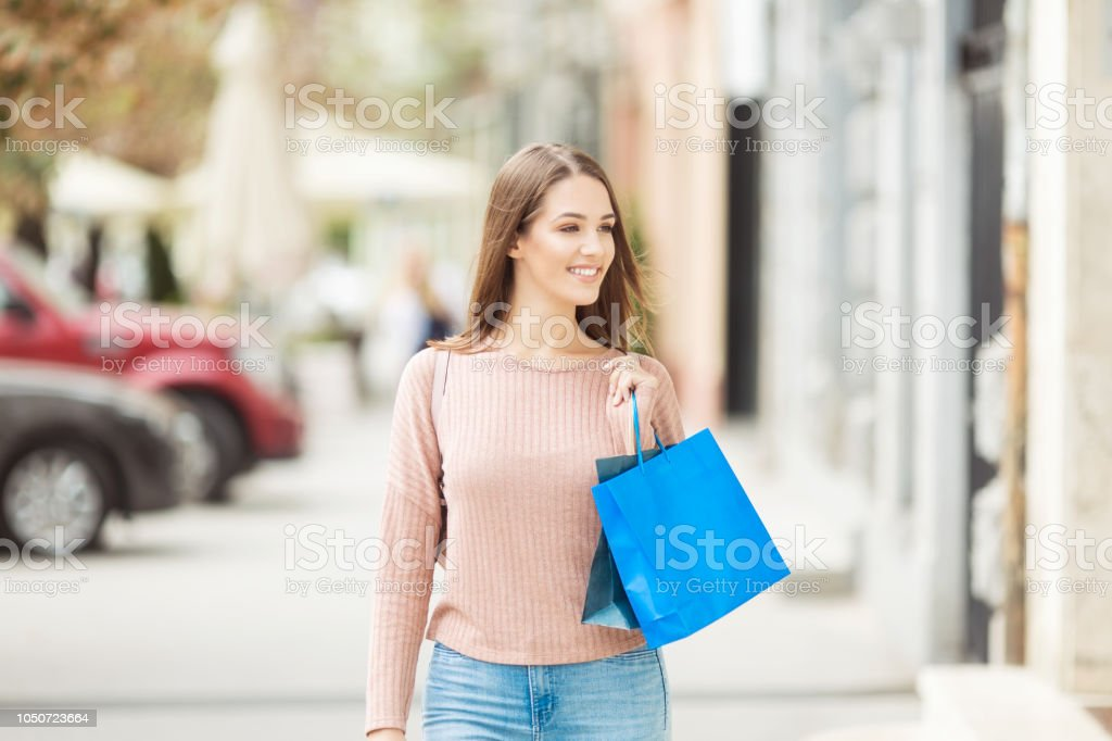 Young woman with shopping bag smiling outdoors stock photo