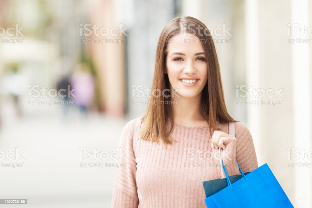 Young woman with shopping bag standing outdoors stock photo