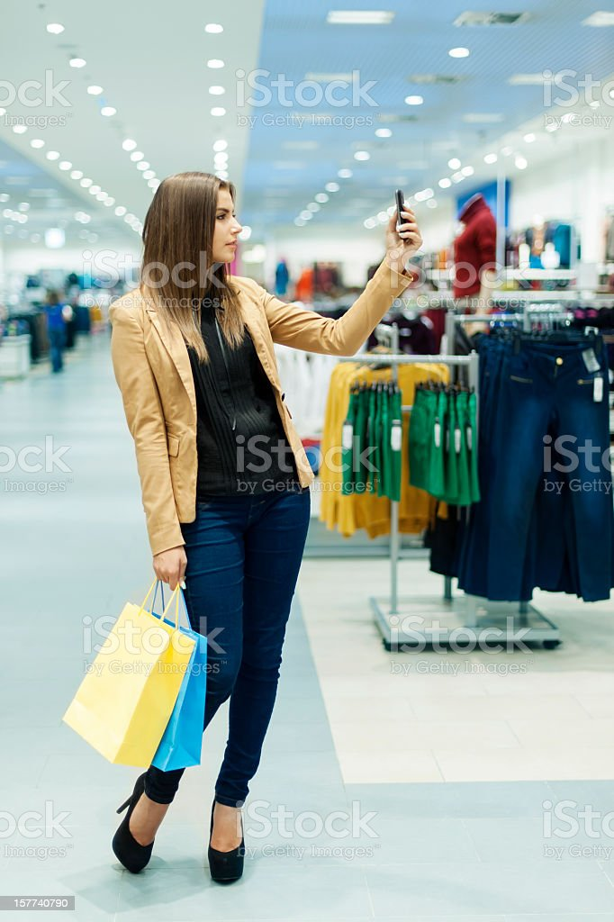 Young woman with shopping bags in a mall taking a selfie royalty-free stock photo