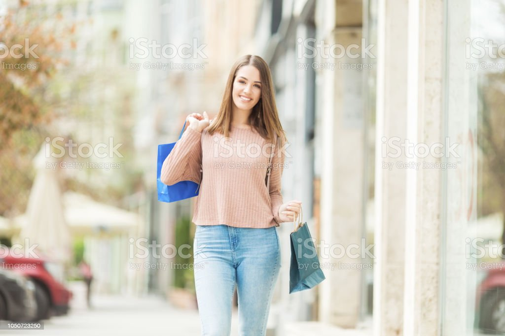 Young woman with shopping bags in front of a store outdoors stock photo