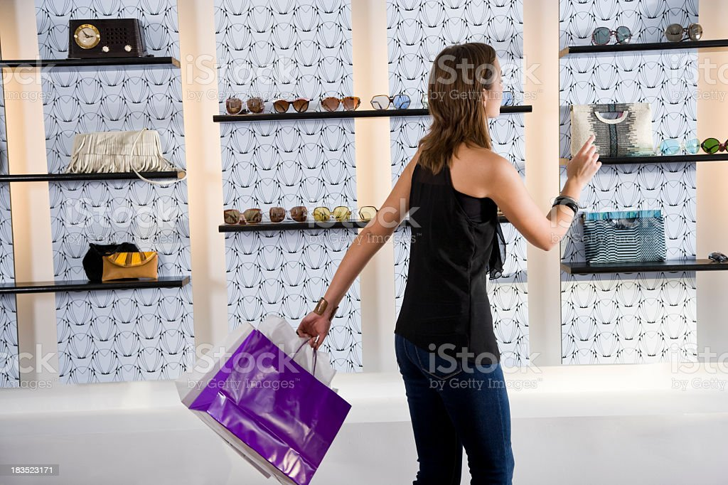 Young woman with shopping bags looking at merchandise in boutique royalty-free stock photo