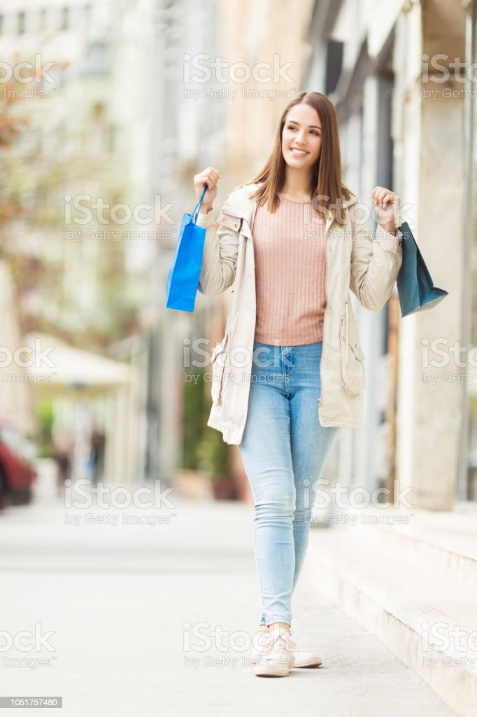 Young woman with shopping bags on the street posing for a camera stock photo