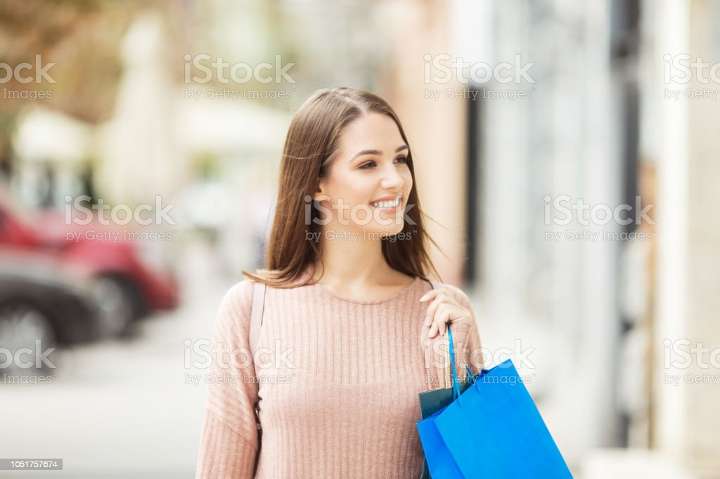 Young woman with shopping bags on the street smiling stock photo
