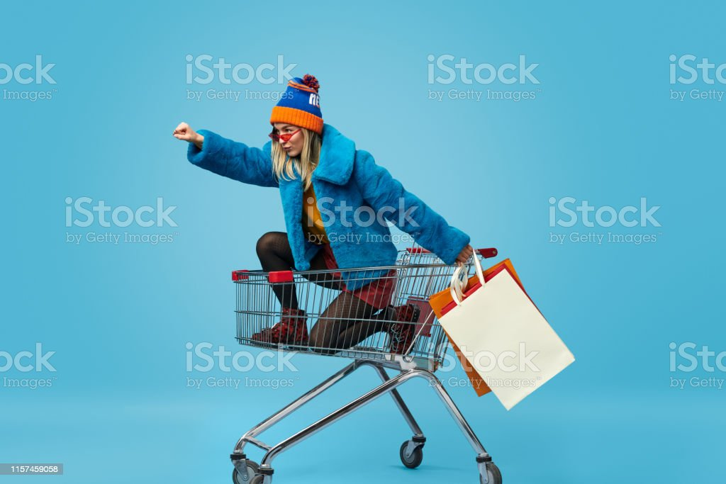 Young woman with shopping bags riding trolley - Royalty-free Adult Stock Photo