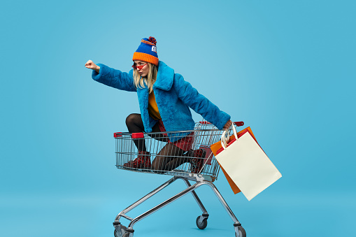 Side view of crazy trendy young female in bright clothes holding paper bags and riding shopping cart in superhero pose against blue background