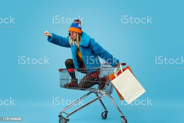 Young Woman With Shopping Bags Riding Trolley Stock Photo - Download Image Now