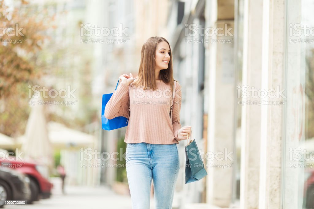 Young woman with shopping bags smiling in front of a store outdoors stock photo