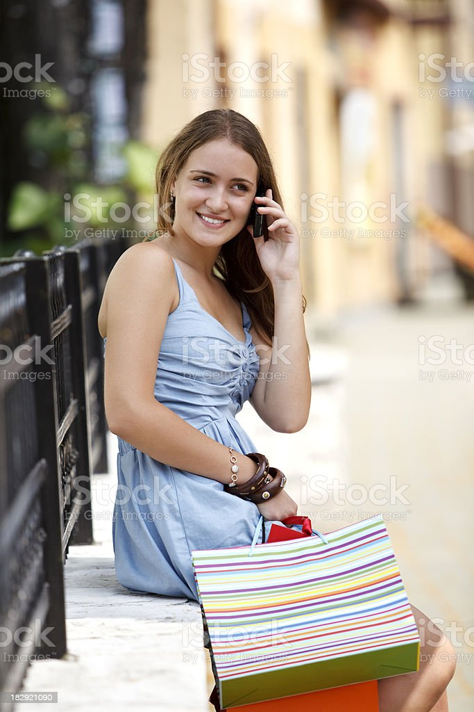 Young woman with shopping bags talking on mobile phone royalty-free stock photo