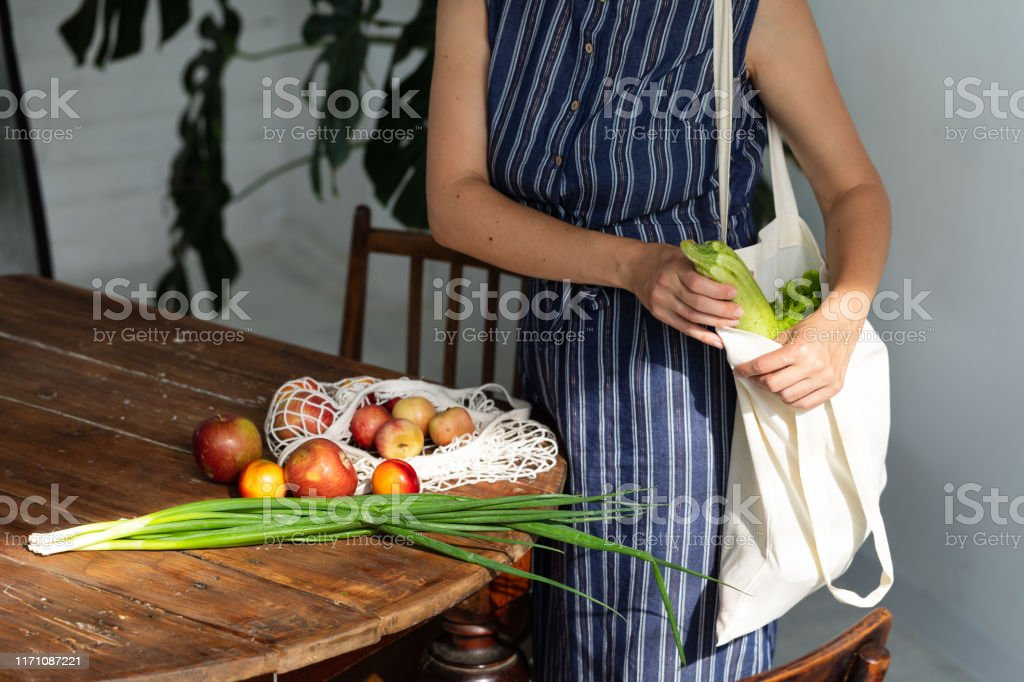 Young woman with shopping cotton Eco bag with fruits and vegetables in her hands near wooden table at home. Lifestyle, zero waste concept - Foto stock royalty-free di Adulto